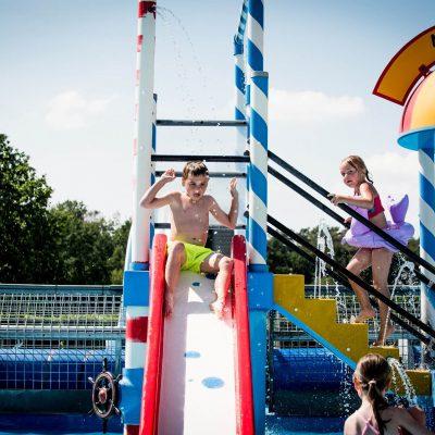 Het kinderzwembad heeft een speeltoestel met glijbaan